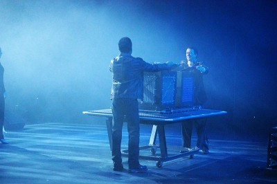Andre and Tim on stage with prop, bathed in blue light, taken from the wings